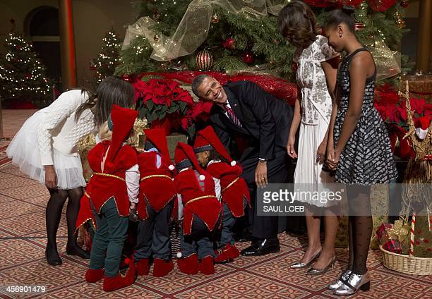President Barack Obama helps children dressed as elves, who are or were patients at Children's National Medical Center, as they present donated gifts...