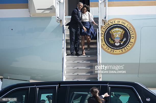 US President Barack Obama helps first lady Michelle Obama as the wind blows her skirt at AustinBergstrom International Airport April 10 2014 in...
