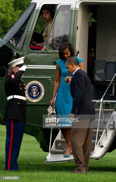 President Barack Obama helps his wife Michelle disembark from Marine One at the White House in Washington on May 5, 2012 after returning from...