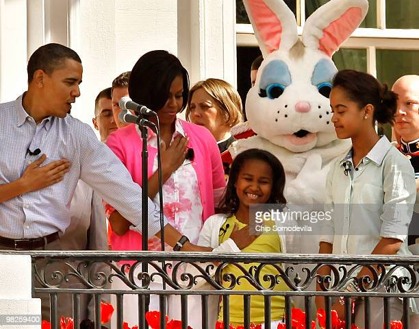 S President Barack Obama helps his younger daughter Sasha Obama put the proper hand over her heart during the singing of the national anthem with...