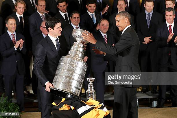 S President Barack Obama helps National Hockey League champion Pittsburgh Penguins Centre Sidney Crosby replace the Stanley Cup while celebrating his...