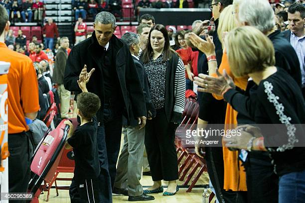 President Barack Obama high-fives a boy as he arrives at a men's NCCA basketball game between the University of Maryland and Oregon State University,...