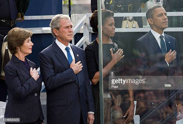 S President Barack Obama his wife Michelle Obama former President George W Bush and his wife Laura Bush salute as the national anthem is played...