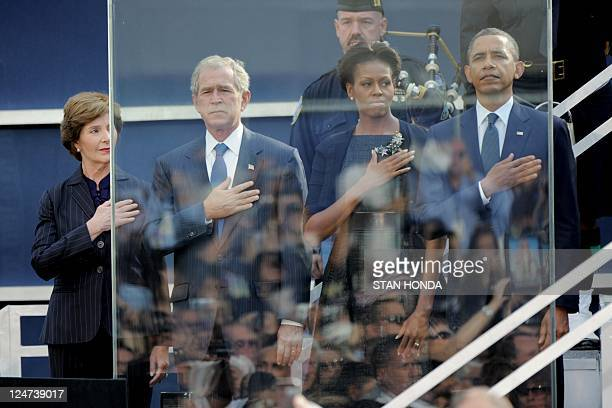 US President Barack Obama his wife Michelle Obama Former US President George W Bush and his wife Laura Bush salute as the national anthem is played...