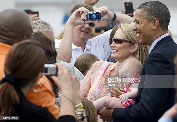 US President Barack Obama holds a baby as he greets guests upon arrival on Air Force One at Tampa International Airport in Tampa Florida on April 13...