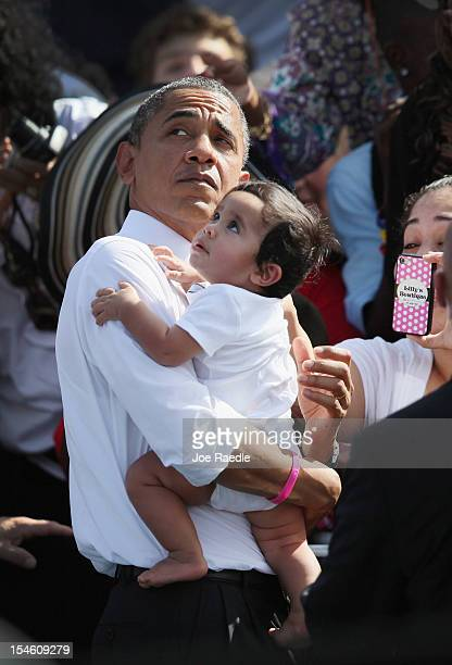 S President Barack Obama holds a baby as he greets people during a campaign rally at the Delray Beach Tennis Center on October 23 2012 in Delray...