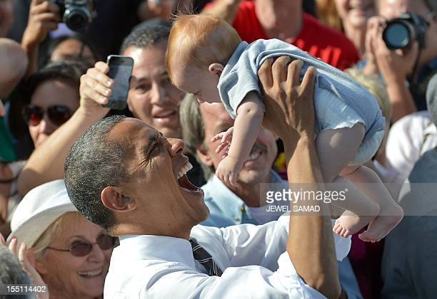 US President Barack Obama holds a baby as he greets supporters during a campaign rally at the Cheyenne Sports Complex in Las Vegas Nevada on November...