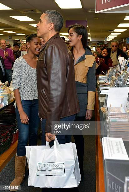 US President Barack Obama holds a bag of his book purchases after he and daughters Malia and Sasha did some shopping at the independent bookstore...