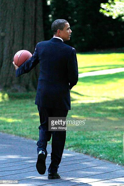 S President Barack Obama holds a basketball as he walks toward the Oval Office after he hosted Detroit Shock at the South Portico of the White House...