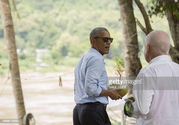US President Barack Obama holds a coconut to drink with US Ambassador to Laos Daniel Clune as he makes a surprise stop for a drink alongside the...