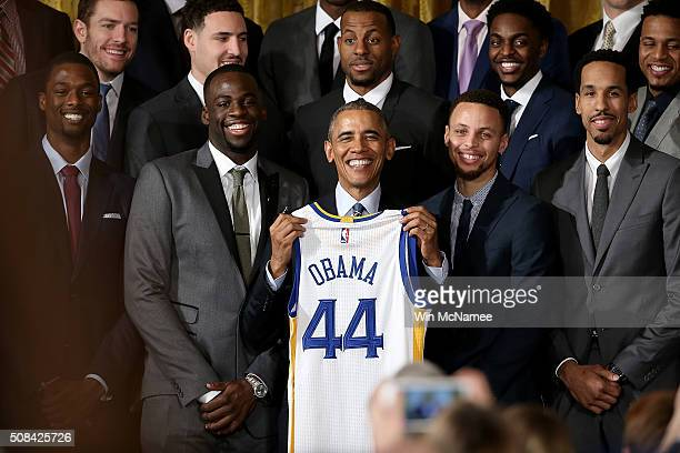 S President Barack Obama holds a Golden State Warriors basketball jersey presented to him during an event with the team in the East Room on February...