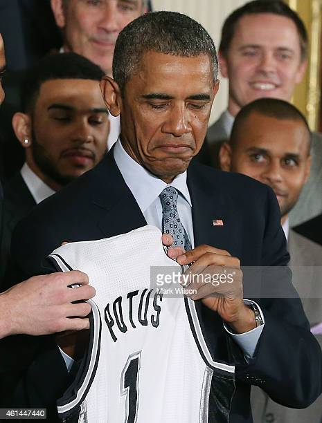 S President Barack Obama holds a jersey given to him by the 2014 NBA Champion San Antonio Spurs in the East Room at the White House January 12 2015...