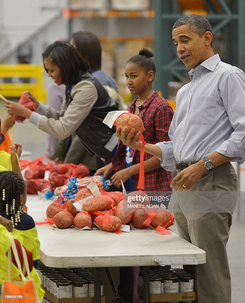 US President Barack Obama holds a sweet potato before distributing it as daughter Sasha, and First Lady Michelle Obama assist at the Capitol Area Food Bank on November 21, 2012, a day ahead of Thanksgiving, in Washington, DC. AFP PHOTO/Mandel NGAN