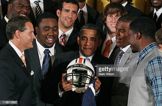 President Barack Obama holds an Auburn Tigers helmet given to him by members of the 2011 BCS National Champion Auburn University football team as he...