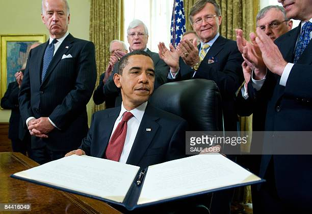 US President Barack Obama holds an executive order related to the closing of the 'War on Terror' prison at Guantanamo Bay Cuba after signing it...