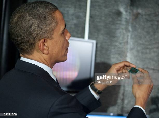 US President Barack Obama holds an Intel microchip as he tours a semiconductor manufacturing facility at Intel in Hillsboro Oregon February 18 2011...