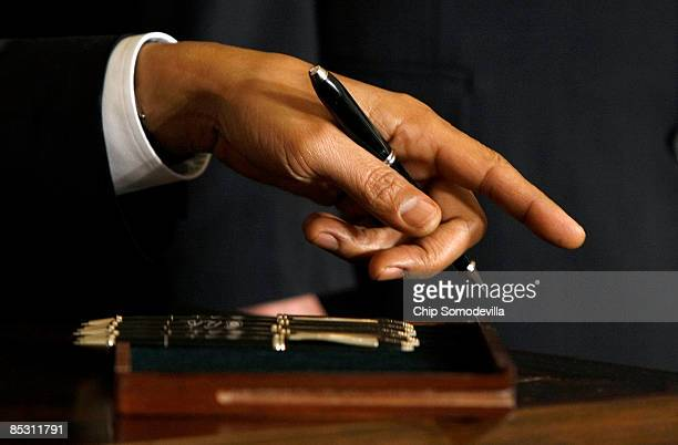 S President Barack Obama holds one of six pens he will use to sign an Executive Order reversing the US government�s ban on funding stemcell research...