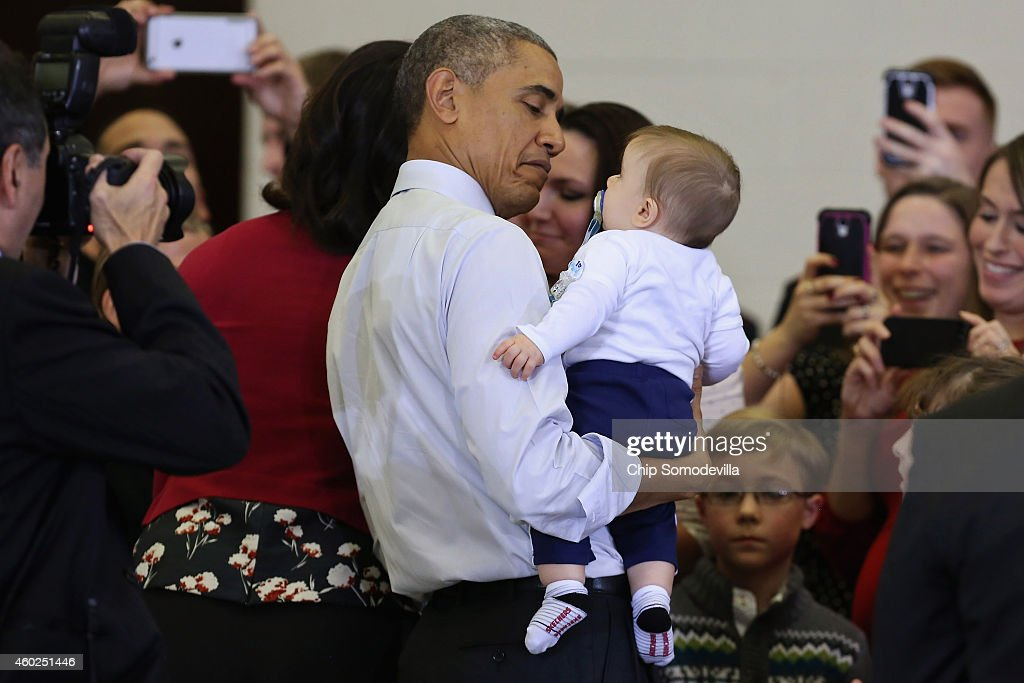 U.S. President Barack Obama holds six-month-old William Gettle after he and first lady Michelle Obama delivered toys and gifts donated by Executive Office of the President staff to the Marine Corps Reserve Toys for Tots Program at Joint Base Anacostia-Bolling December 10, 2014 in Washington, DC. For 67 years the Toys for Tots program has worked with local communities to collect and distribute toys and gifts for less fortunate children throughout the United States.