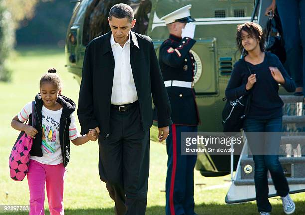 President Barack Obama holds the hand of his daughter Sasha as daughter Malia walks off Marine One to the White House November 8 2009 in Washington...