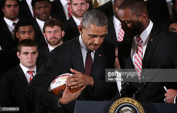 S President Barack Obama holds tight a football that he receives from Curtis Grant of the Ohio State University Buckyes football team during an East...