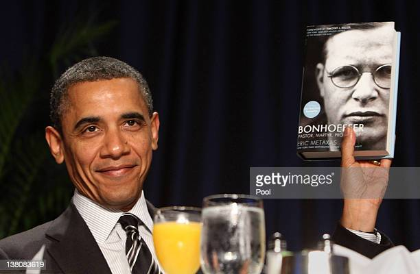 US President Barack Obama holds up a book given to him by author Eric Metaxas who was the keynote speaker at the National Prayer Breakfast February 2...