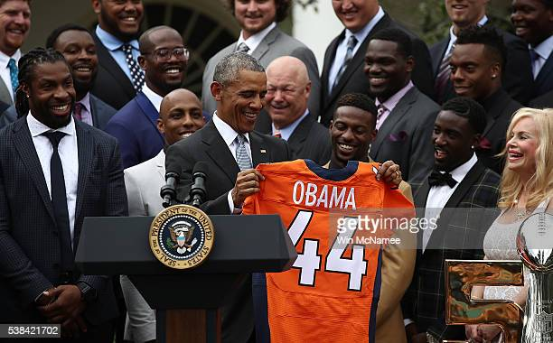 S President Barack Obama holds up a Denver Broncos jersey presented to him as a gift by Annabel Bowlen wife of Broncos majority owner Pat Bowlen...