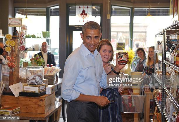 US President Barack Obama holds up a jar of salsa while shopping at the Golden Fig food store in St Paul Minnesota on June 26 2014 The store offers...
