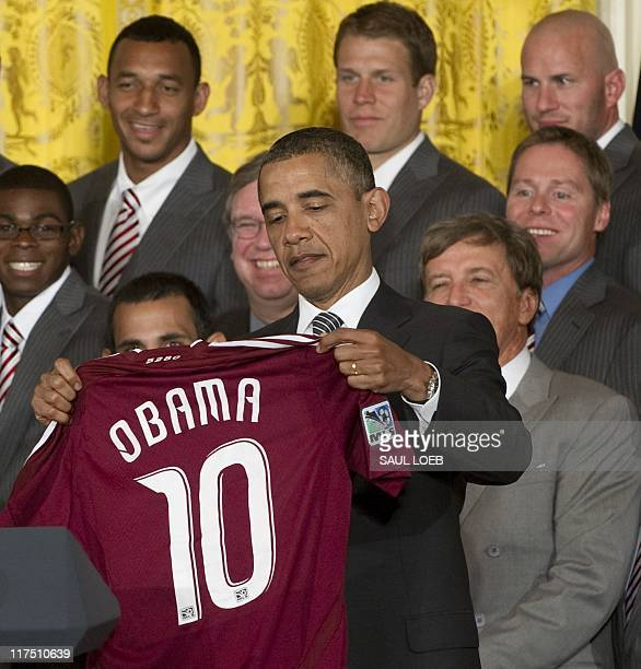 US President Barack Obama holds up a soccer jersey presented to him by the Colorado Rapids during a ceremony honoring the team for their 2010 Major...