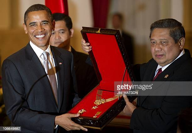 US President Barack Obama holds up an award for his mother Stanley Ann Dunham from Indonesian President Susilo Bambang Yudhoyono during a state...