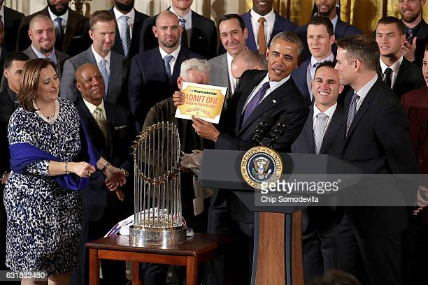 S President Barack Obama holds up his lifetime ticket given to him by Major League Baseball World Series champion Chicago Cubs coowner Laura Ricketts...