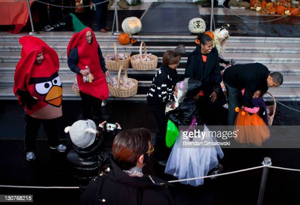 S President Barack Obama hugs a trick or treater while greeting others with first lady Michelle Obama and her mother Marian Robinson at the White...