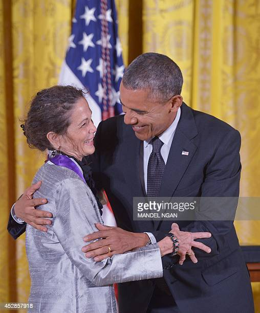 US President Barack Obama hugs Julia Alvarez novelist poet and essayist after presenting her with the National Medal of Arts during a ceremony in the...