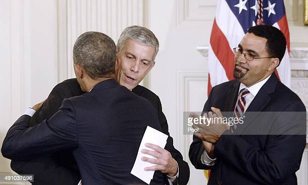 President Barack Obama hugs outgoing Secretary of Education Arne Duncan as his nominee to replace Duncan, John B. King Jr. Looks on in the State...