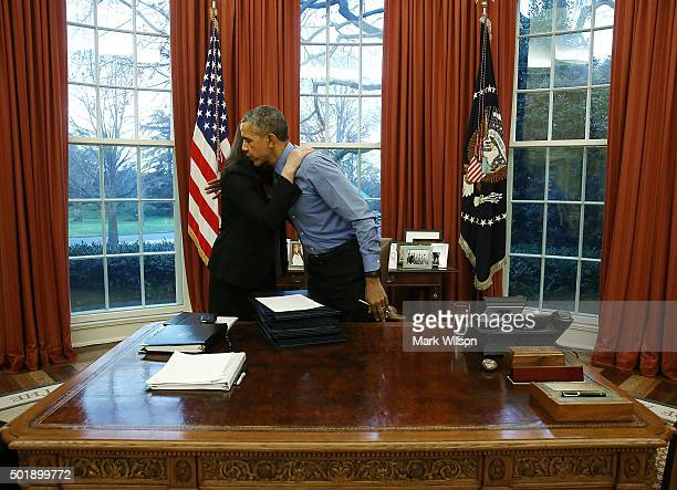 S President Barack Obama hugs Staff Secretary Joani Walsh after signing 12 bills at his desk in the Oval Office at the White House December 18 2015...