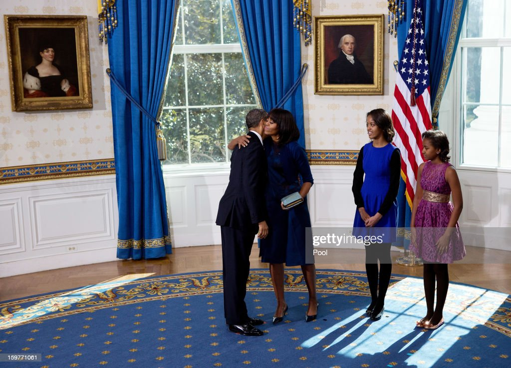 President Barack Obama (L) hugs the first lady Michelle Obama (2nd L) as daughters Malia (C) and Sasha look on after taking the oath of office in the Blue Room of the White House January 20, 2013 in Washington, DC. Obama and U.S. Vice President Joe Biden were officially sworn in a day before the ceremonial inaugural swearing-in.