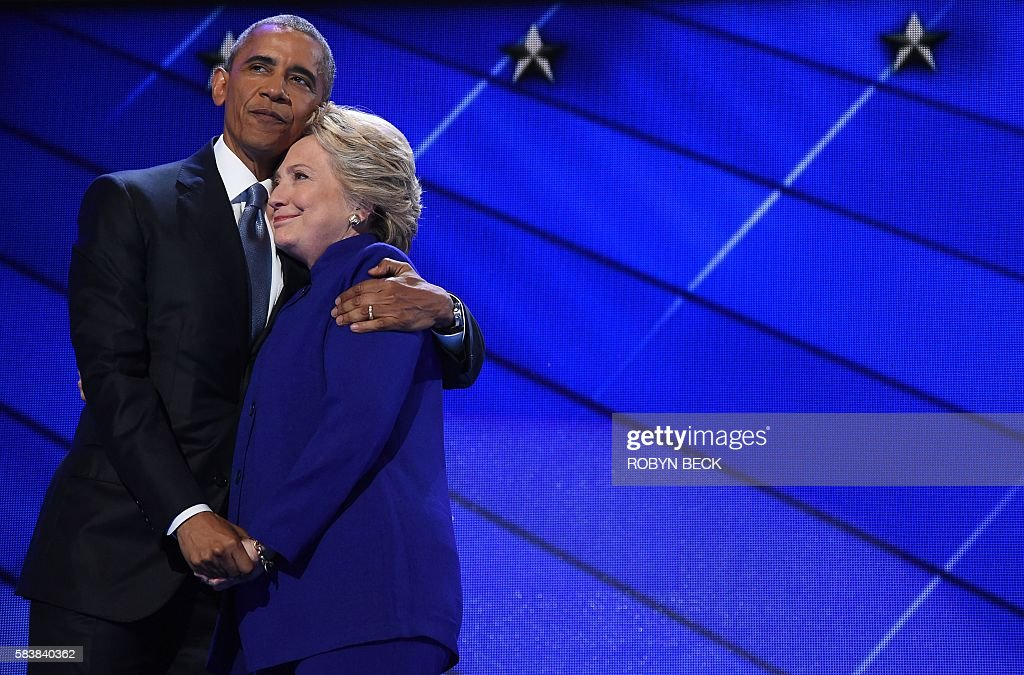 President Barack Obama (L) hugs US Presidential nominee Hillary Clinton during the third night of the Democratic National Convention at the Wells Fargo Center in Philadelphia, Pennsylvania, July 27, 2016. / AFP / Robyn BECK