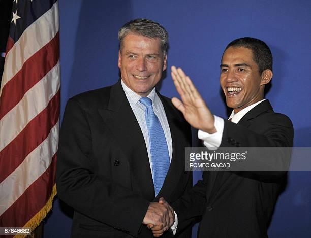 US President Barack Obama impersonator Indonesian Ilham Anas welcomes US Ambassador Cameron Hume at the film premier of the documentary Amerikaku...