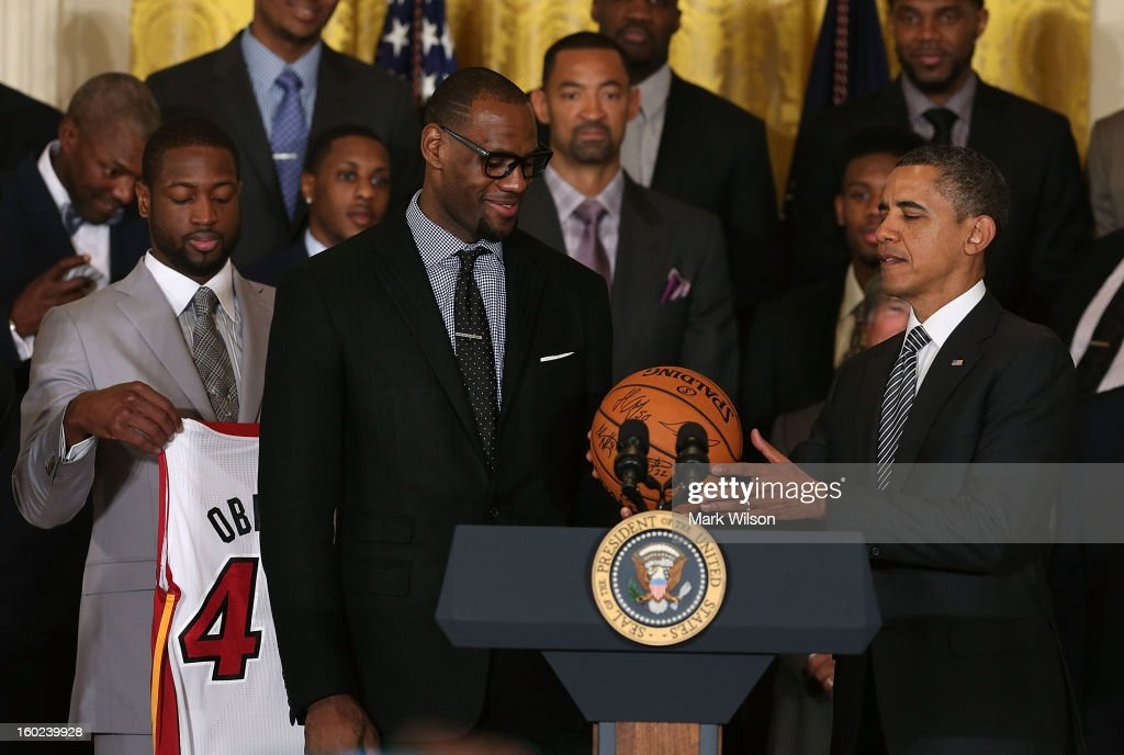 U.S. President Barack Obama (R) is given a ball from LeBron James (L) during an event to honor the NBA champion Miami Heat in the East Room at the White House on January 28, 2013 in Washington, DC. President Barack Obama congratulated the 2012 NBA champions for claiming their third NBA Championship by beating the Boston Celtics.