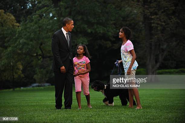 US President Barack Obama is greeted by his daughters Sasha and Malia and their dog Bo upon his return to the White House in Washington on September...