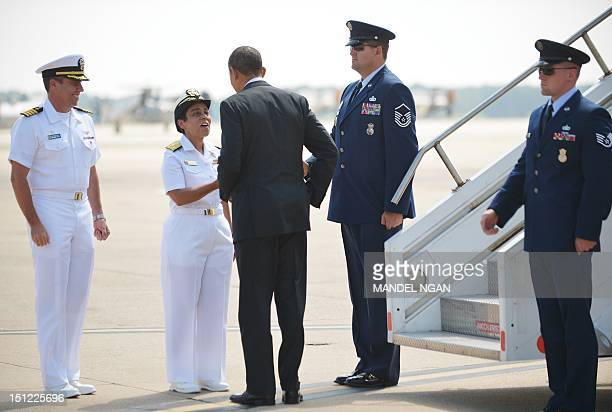 US President Barack Obama is greeted by Vice Admiral Michelle Howard Deputy Commander US Fleet Forces Command and Captain David Culler Commanding...