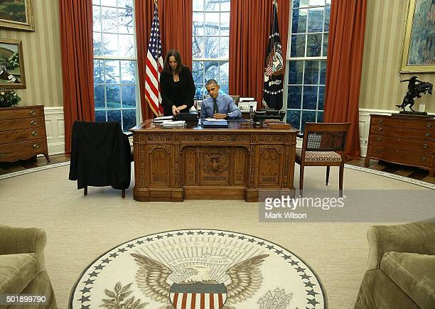 S President Barack Obama is handed one of 12 bills from Staff Secretary Joani Walsh to sign at his desk in the Oval Office at the White House...