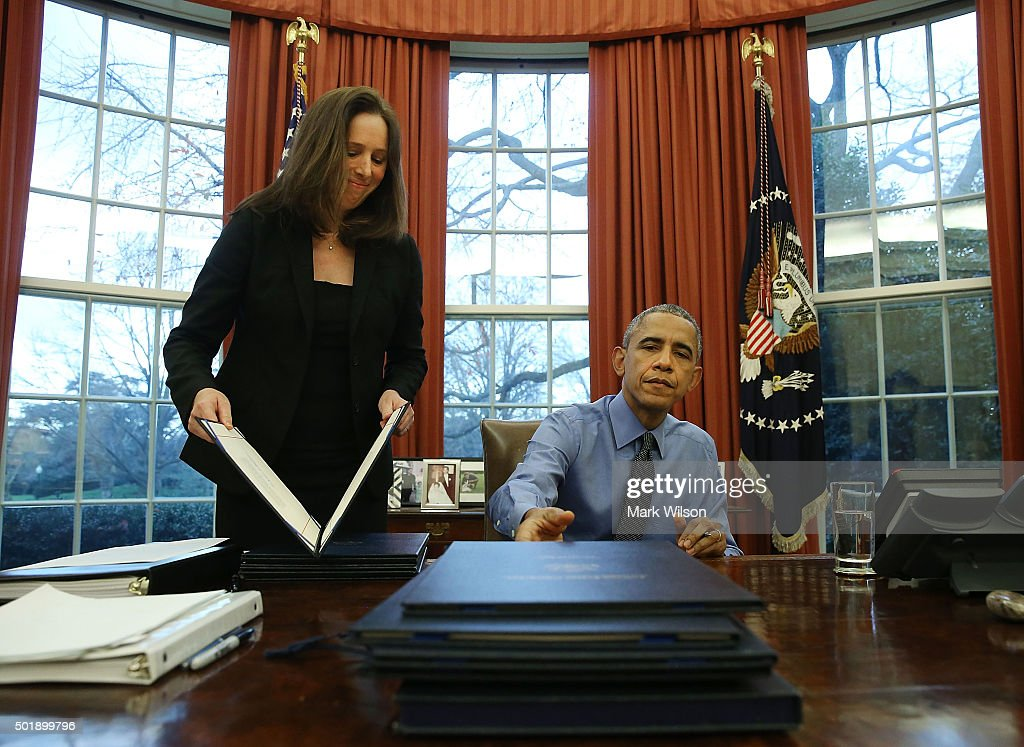 obama oval office. u.s. president barack obama is handed one of 12 bills from staff secretary joani walsh, oval office