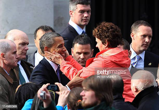 US President Barack Obama is hugged by a woman of the crowd after delivering a speech to crowds of people during a public rally at College Green in...