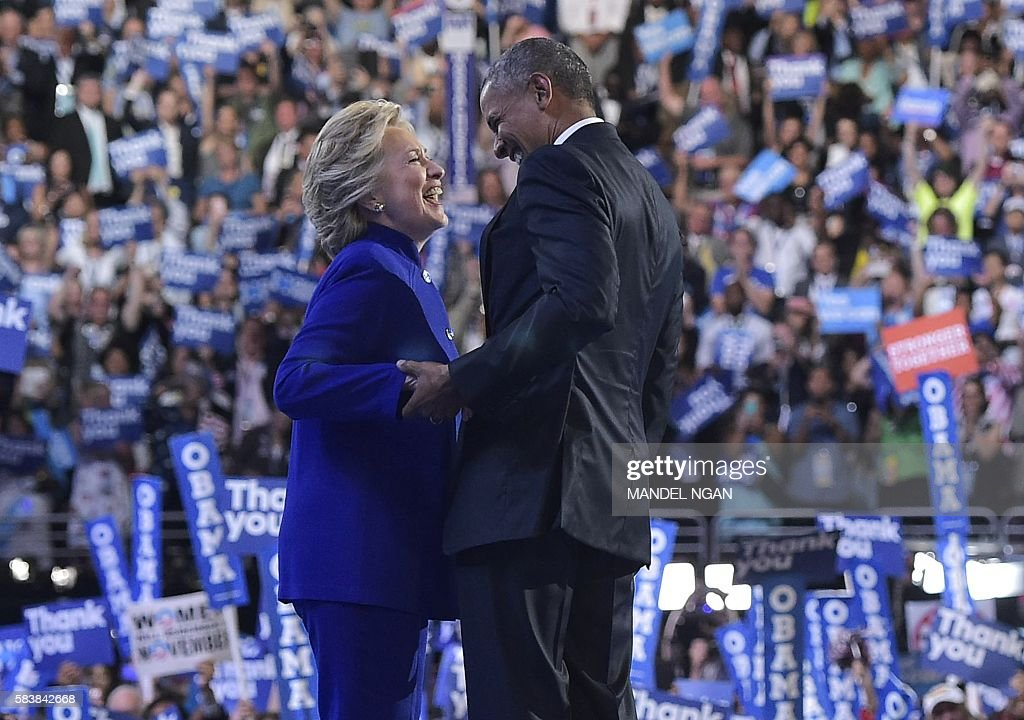 President Barack Obama is joined by US Democratic presidential candidate Hillary Clinton after his address to the Democratic National Convention at the Wells Fargo Center in Philadelphia, Pennsylvania, July 27, 2016. / AFP / MANDEL