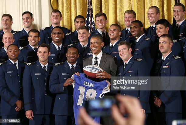President Barack Obama is presented with a football and a jersey after presenting the CommanderinChief trophy to the United States Air Force Academy...