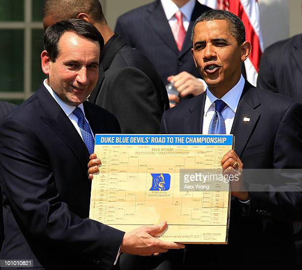 S President Barack Obama is presented with a plaque of a bracket by coach Mike Krzyzewski of the Duke Blue Devils during a Rose Garden event May 27...