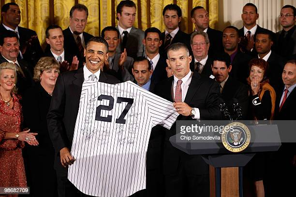President Barack Obama is presented with an autographed New York Yankees jersey by team manager Joe Girardi during a ceremony celebrating the World...
