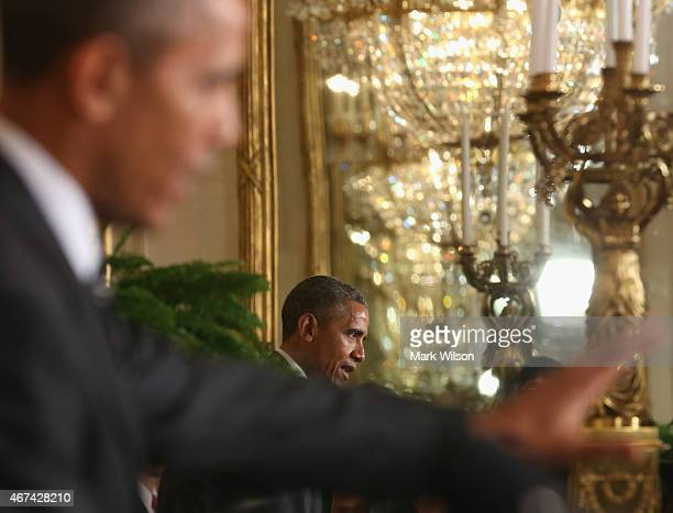 President Barack Obama is reflected in a mirror while speaking at a news conference with Afghan President Ashram Ghani in the East Room at the White...