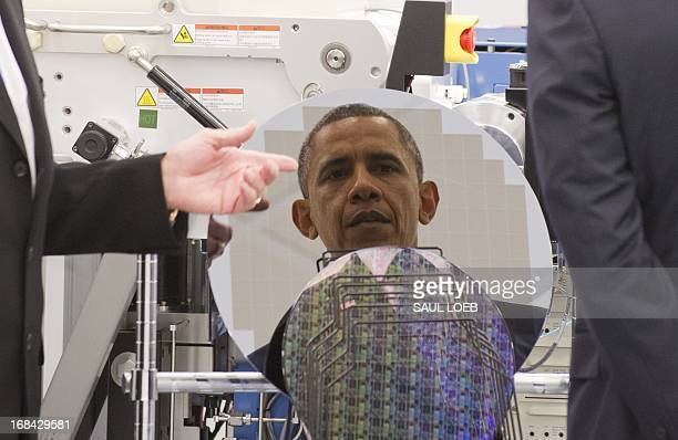 US President Barack Obama is reflected in a silicon wafer as he tours Applied Materials a manufacturer of systems for polishing the surface of...