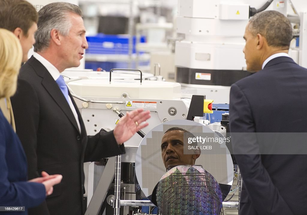 US President Barack Obama is reflected in a silicon wafer as he tours Applied Materials, a manufacturer of systems for polishing the surface of unfinished semiconductor chips, with company CEO Mike Splinter (L) prior to speaking on the economy and job creation in Austin, Texas, May 9, 2013. AFP PHOTO / Saul LOEB